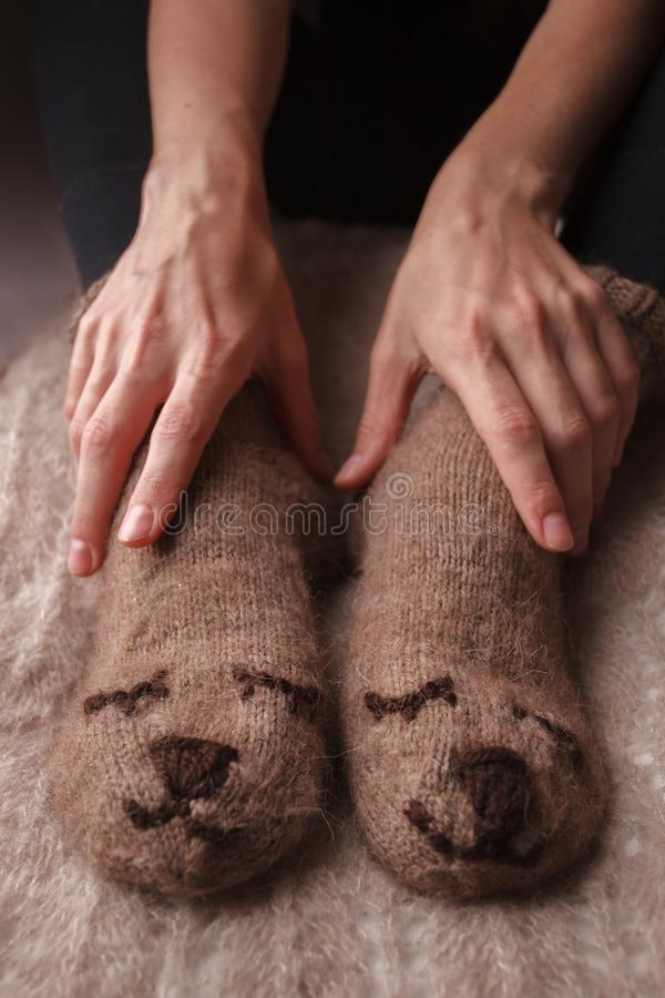 Cozy Winter fall autumn lifestyle: woman feets legs in warm cute bear socks. Retro toning, beige monochrome, hipster still life. royalty free stock photography