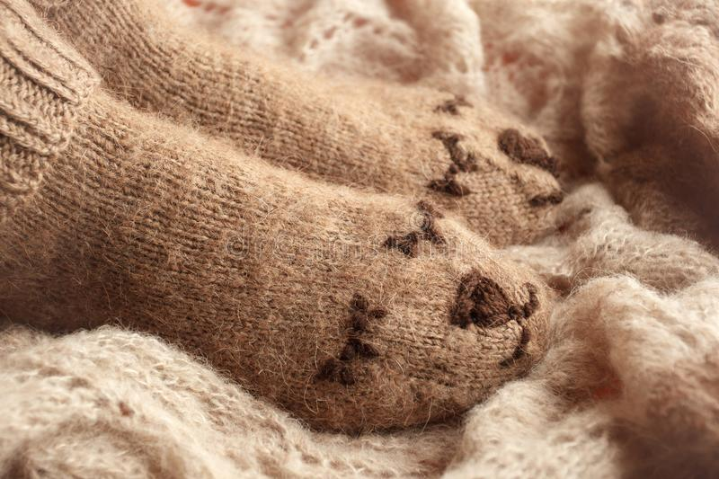 Cozy Winter fall autumn lifestyle: woman feets legs in warm cute bear socks. Retro toning, beige monochrome, hipster still life. Season relax concept royalty free stock photography