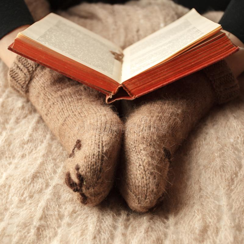 Cozy Winter fall autumn lifestyle: woman in warm cute bear socks with book. Retro toning, beige monochrome, hipster still life. stock image