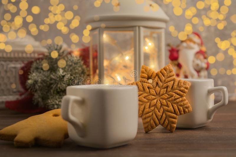 Cozy winter at home with hot drink and cookies. Christmas time with tea and garland royalty free stock photo
