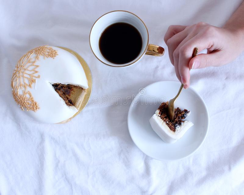 Cozy winter morning breakfast in bed still life scene.Young woman eating yummy cake and coffee. Steaming cup of hot royalty free stock photos