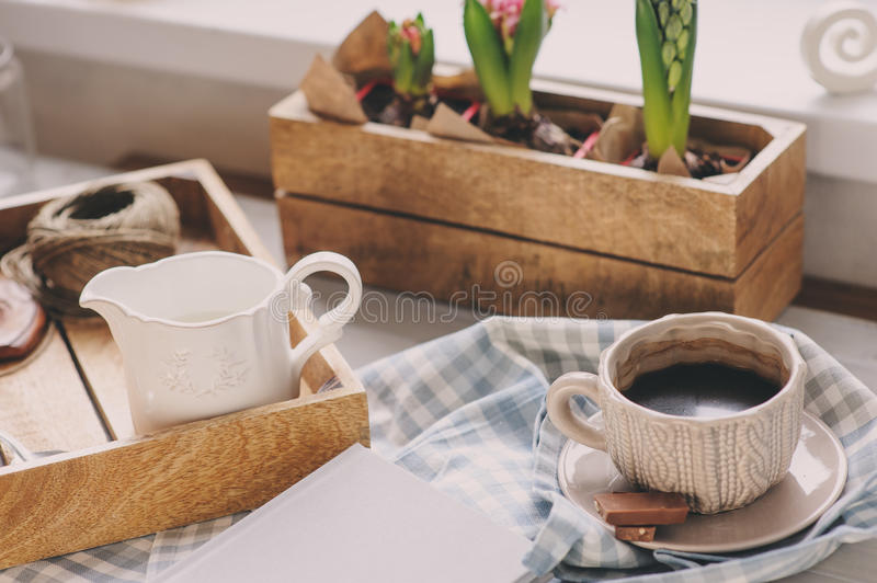 Cozy winter morning at home. Coffee, milk and chocolate on wooden tray. Huacinth flowers on background. Warm mood stock images