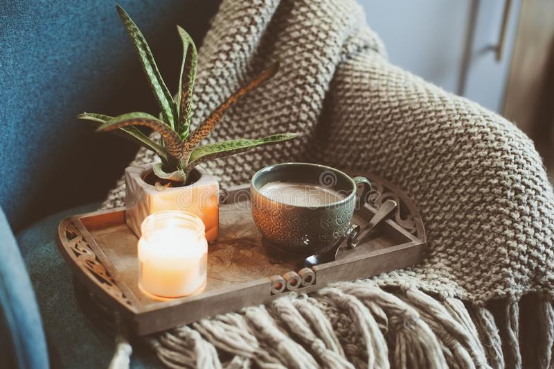 Cozy winter morning at home. Hot cocoa or coffee with candle on blue nordic style chair stock images