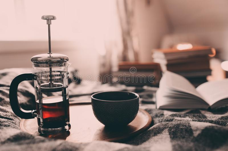 Cozy winter morning at home with hot tea. Having breakfast in bed in real life interior. Relaxing with book stock images