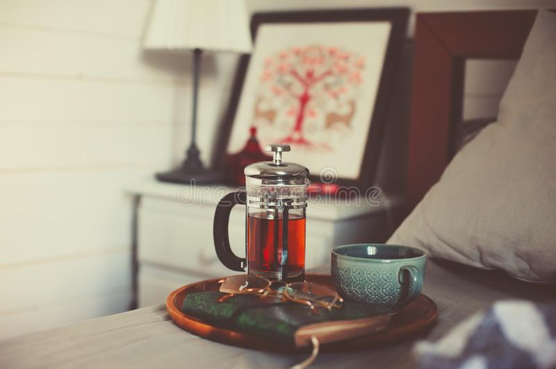 Cozy winter morning at home with hot tea. Having breakfast in bed in real life interior. Relaxing with book royalty free stock image