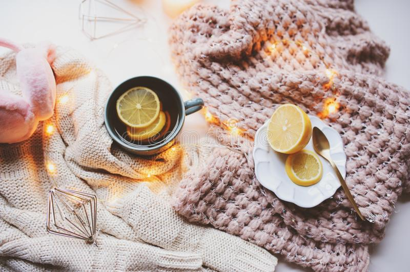 Cozy winter morning at home. Hot tea with lemon, knitted sweaters and modern interior details. Flat lay still life. Composition stock photography