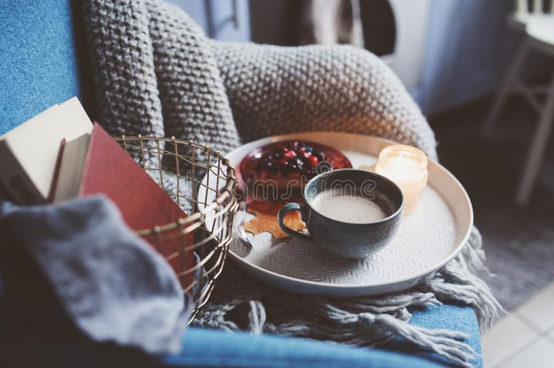 Cozy winter weekend at home. Morning with coffee or cocoa, berry pie, books, warm knitted blanket and nordic style chair. Hygge co royalty free stock image