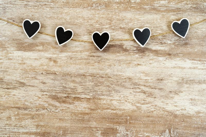 Cozy wooden background, with 5 black hearts fastened between them with a hemp rope, love concept, for Valentine`s Day, royalty free stock photography