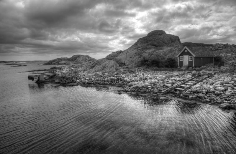 Refuge for bad weather. Cozy wooden refuge between stony coast and sea, ready for an emergency stay. Black and white concept from wild scandinavian country royalty free stock image