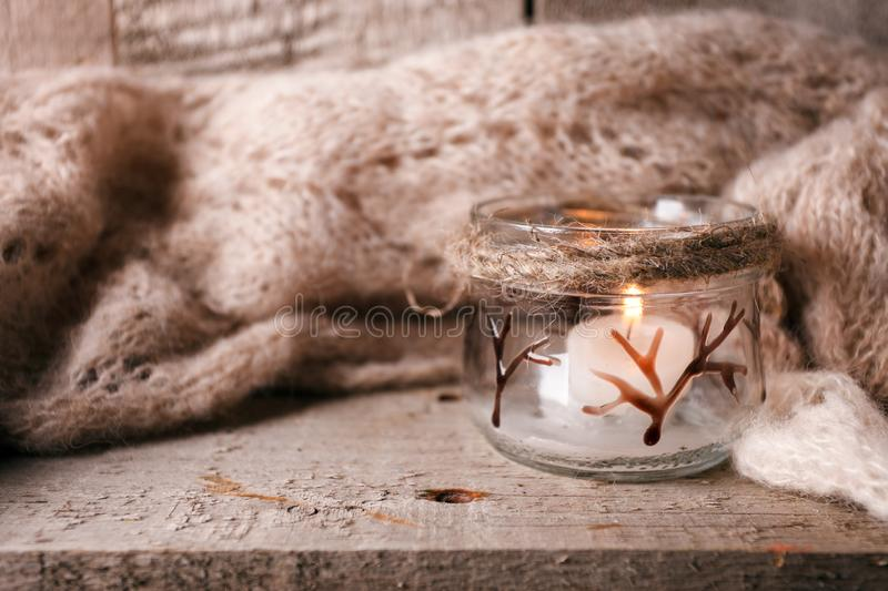 Cozy wool winter autumn fall accessory. Warm pleid and candle on a wooden table. Authentic Tranquil Atmosphere. Kinfolk Hygge Slow stock photo