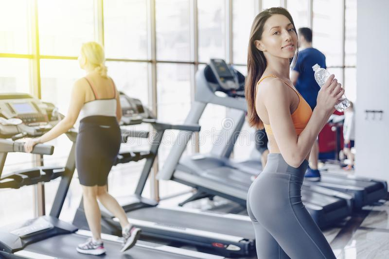 Young attractive girl in the gym drinking water on the background of treadmills stock photos