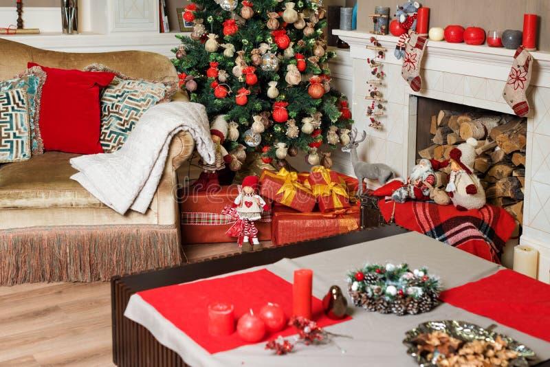 Cozyness en huiscomfort Bank dichtbij de verfraaide Kerstboom en open haard met brandhout De ruimtebinnenland van de de wintervak stock afbeeldingen