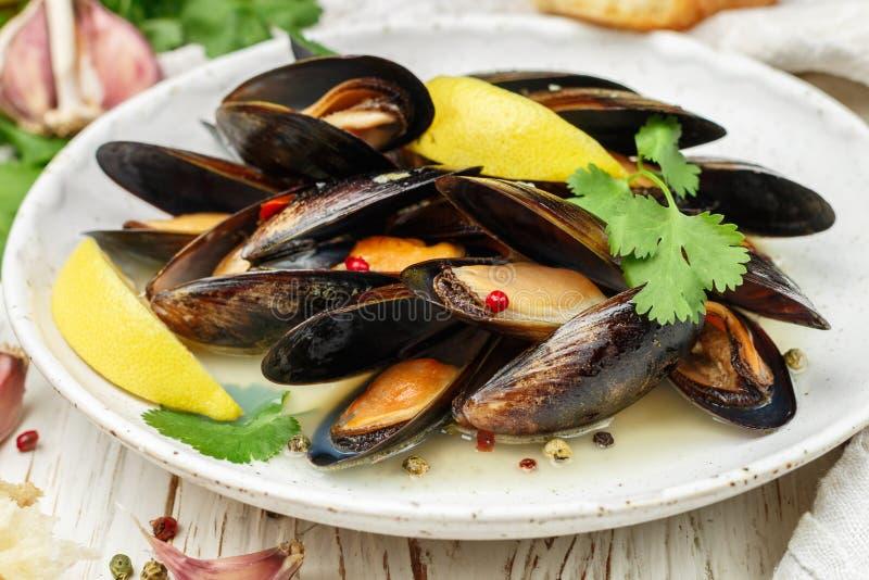 Cozze deliziose in vino bianco con il limone, l'aglio, le erbe e le spezie in un piatto bianco fotografia stock