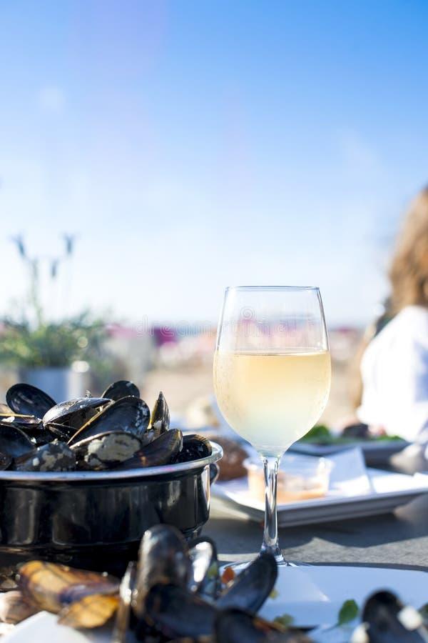 Cozze in una casseruola ed in un vetro di vino bianco freddo Cena deliziosa dei frutti di mare in un ristorante sulla spiaggia Co fotografie stock