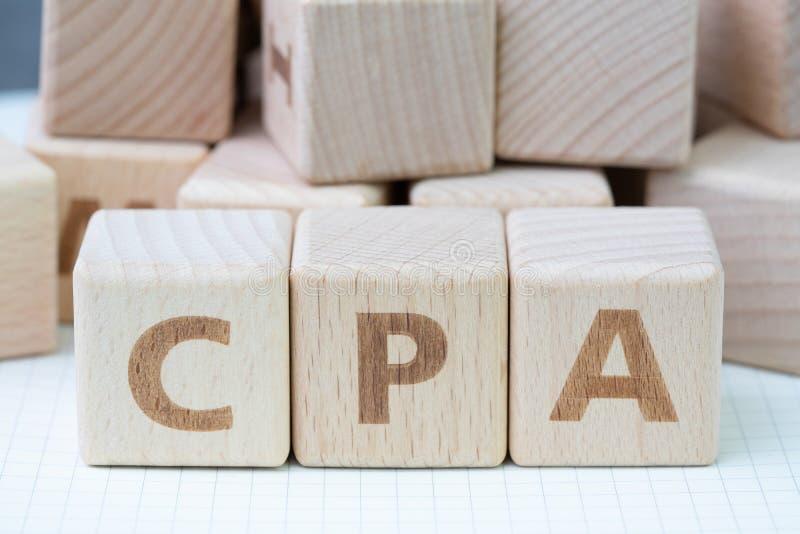 CPA, expert-comptable certifié ou coût par concept d'action, mot en bois CPA, certificat de bâtiment de bloc de cube employant po photo libre de droits