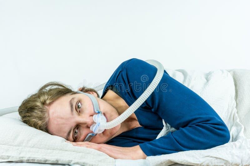 CPAP, traitement d'apnée du sommeil La femme s'étendant de son côté avec des yeux s'ouvrent images stock