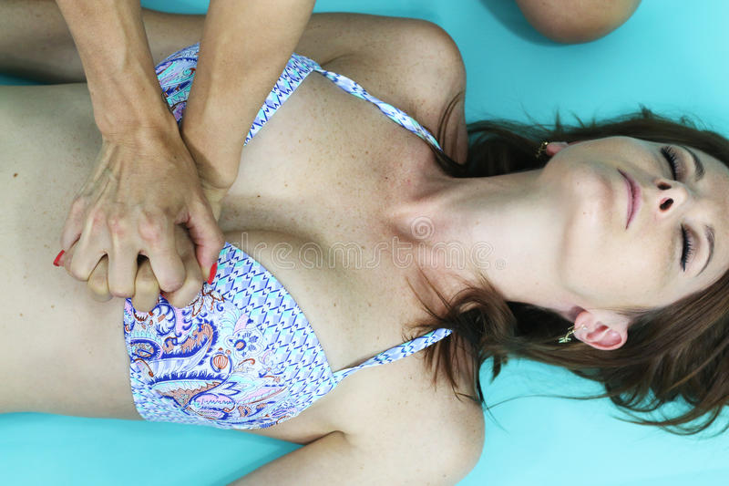 CPR - chest compressions on a young woman. Chest compressions on a young woman over a blue background stock photo