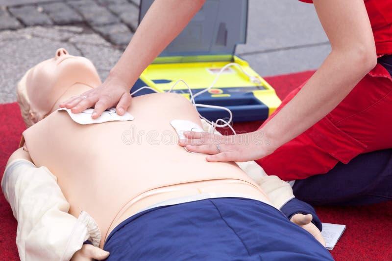 Cpr-kurs genom att använda den automatiserade yttre defibrillatorapparaten - AED royaltyfri foto