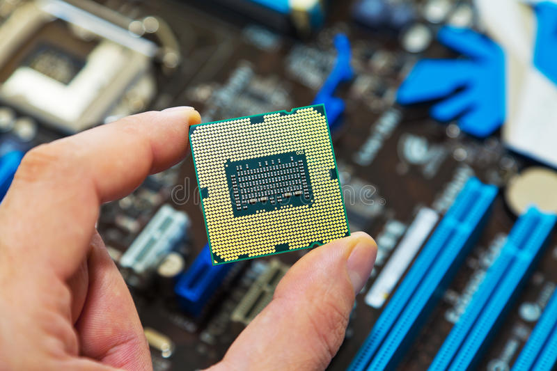 CPU in hand. Macro view of CPU in hand with motherboard in background royalty free stock image