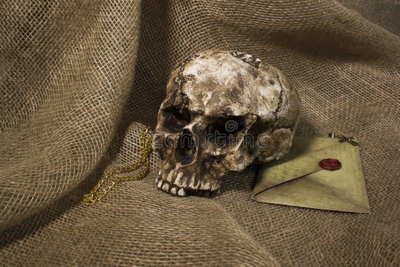 Cráneo dañado con una letra, con un fondo de la arpillera fotos de archivo libres de regalías