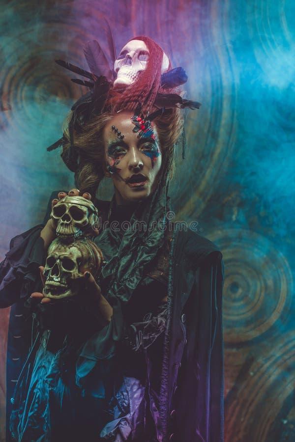 Cráneo hloding de la bruja joven Brillante componga y fume el tema de Halloween imagen de archivo