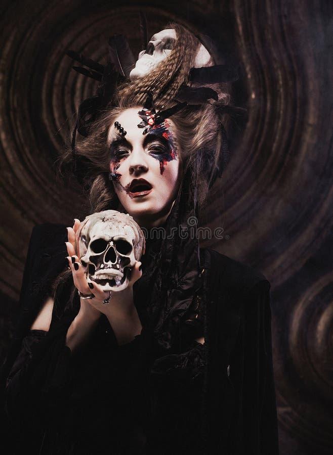 Cráneo hloding de la bruja joven Brillante componga y fume el tema de Halloween imagenes de archivo