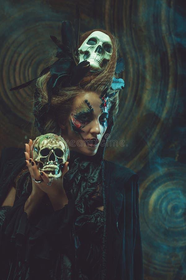 Cráneo hloding de la bruja joven Brillante componga y fume el tema de Halloween fotos de archivo libres de regalías