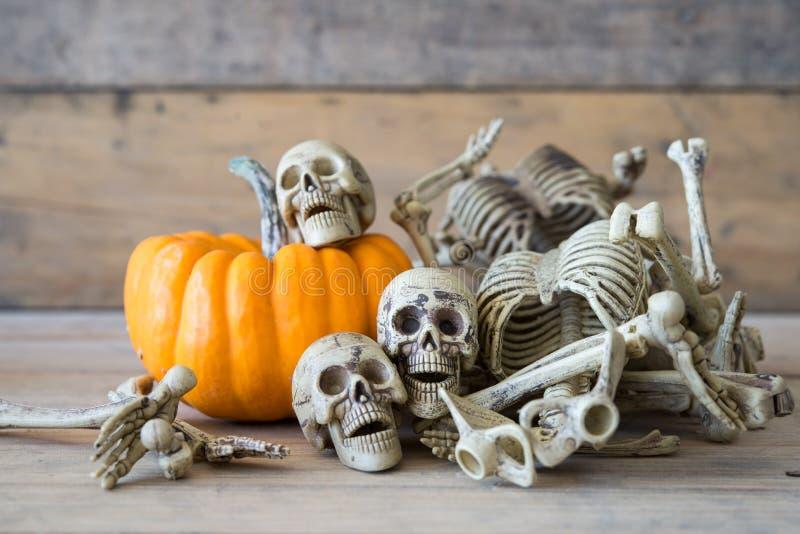 Cráneo humano en el fondo, el esqueleto y la calabaza de madera en la madera, fondo del feliz Halloween imagenes de archivo