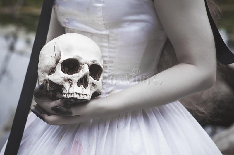 Cráneo humano en manos espeluznantes de la novia Concepto de Víspera de Todos los Santos imagenes de archivo