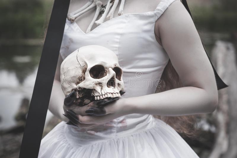 Cráneo humano en manos espeluznantes de la novia Concepto de Víspera de Todos los Santos foto de archivo libre de regalías