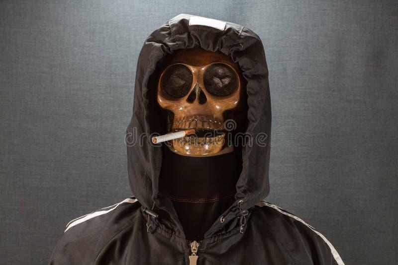 Cráneo humano que fuma un cigarrillo en un fondo negro, cigarrillo muy peligroso para la gente No fume por favor Día de Halloween imagen de archivo libre de regalías