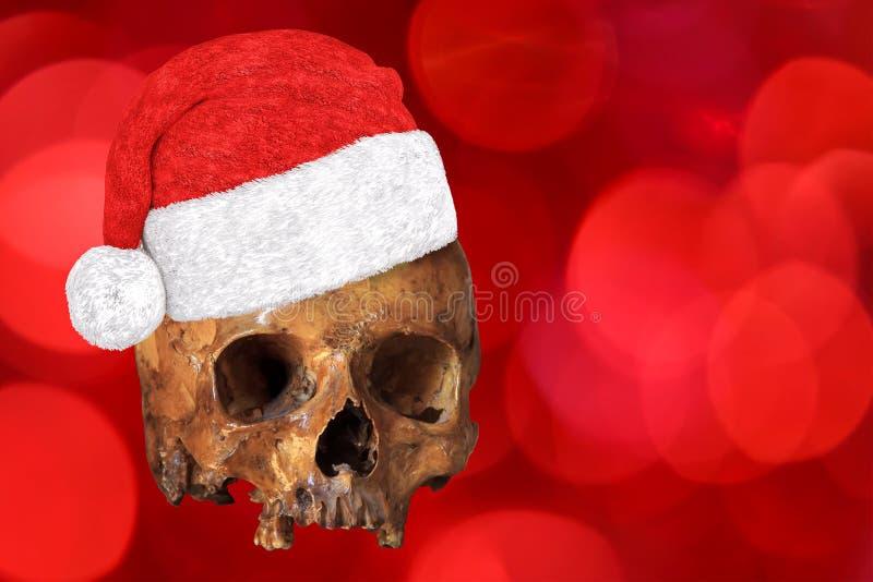 Cráneo humano que lleva Navidad o el sombrero de la Navidad en fondo rojo del bokeh Puede ser utilizado para agujerear el día de  libre illustration