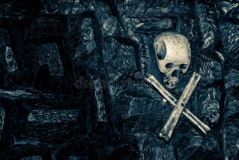 Cráneo y bandera pirata que cuelgan en una roca oscura imágenes de archivo libres de regalías