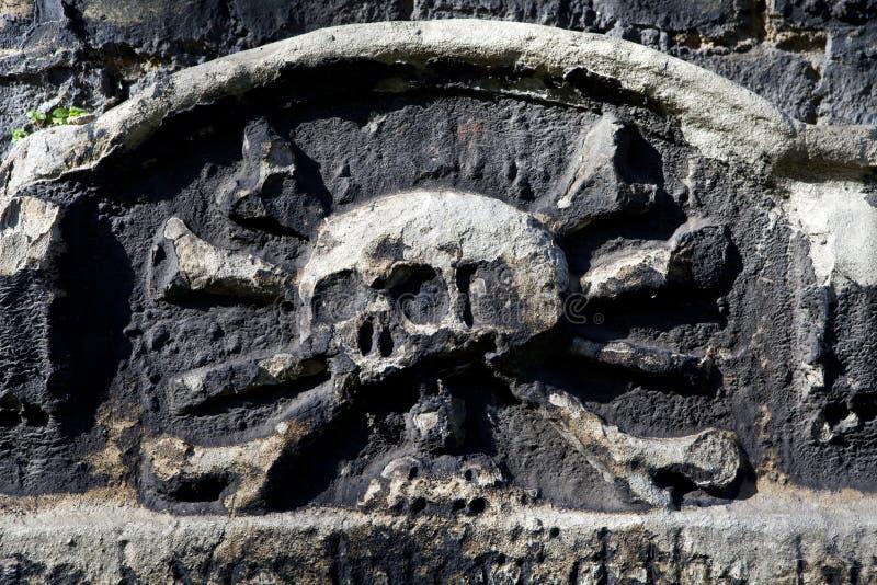 Cráneo y bandera pirata que tallan en una lápida mortuaria fotografía de archivo