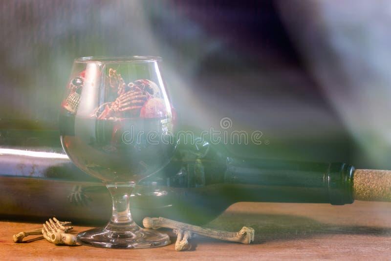 Cráneos en el vidrio y el vino de la sangre en la tabla de madera fotos de archivo