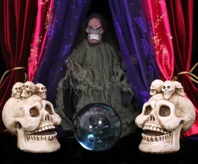 Cráneos y bola cristalina imagen de archivo