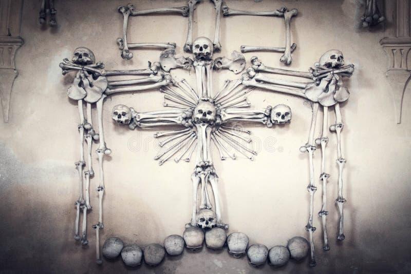 Cráneos y huesos cubiertos en la porción del polvo de restos humanos espeluznantes en oscuridad Fondo oscuro abstracto que simbol fotografía de archivo