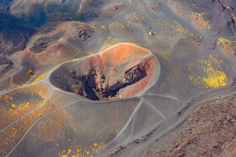 Cráter volcánico en el lado de la montaña, alrededor de lava endurecida. Silueta del hombre de negocios Cowering fotos de archivo libres de regalías