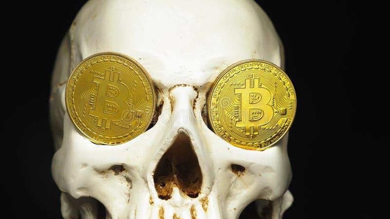 Crâne avec des factures de dollar US dans sa bouche bitcoins sur les yeux photographie stock libre de droits