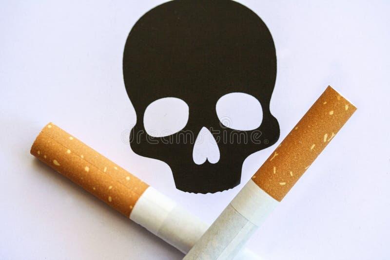Crâne de cigarettes et os de croix photo stock