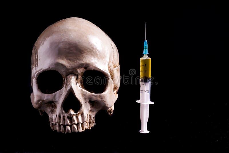 Crâne et seringue de liquide jaunâtre photos libres de droits