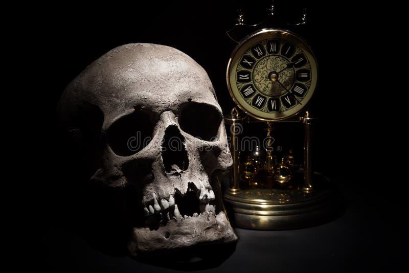 Crâne humain avec la fin d'horloge de vintage sur le fond noir photos stock