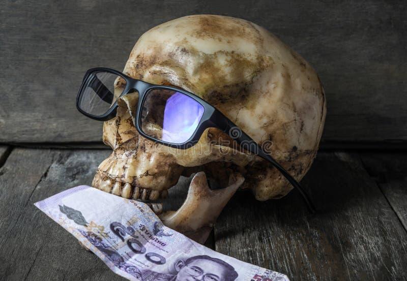 Crâne humain d'homme d'affaires mangeant l'argent photos stock