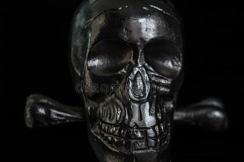 Crânio do metal no fundo preto foto de stock