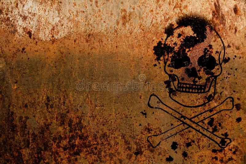 Crânio e ossos cruzados simbólicos para o perigo e risco de vida pintado sobre um fundo oxidado da textura da placa de metal imagens de stock royalty free