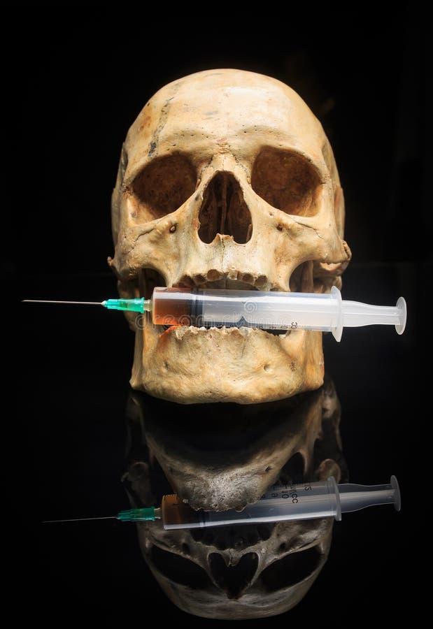 Crânio e seringa do líquido amarelado Conceito fotos de stock