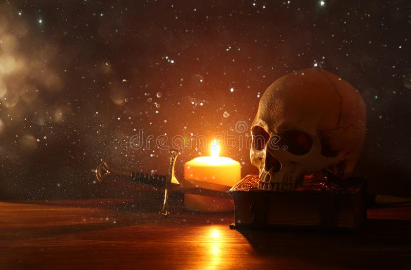 Crânio humano, livro velho, espada e vela ardente sobre a tabela de madeira velha e o fundo escuro imagem de stock royalty free