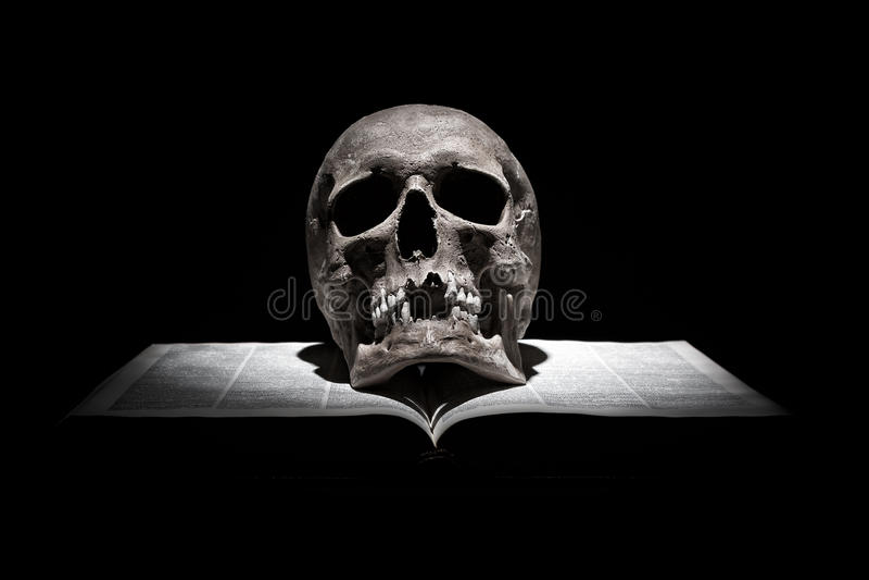 Crânio humano no livro aberto velho no fundo preto sob o feixe de luz imagem de stock