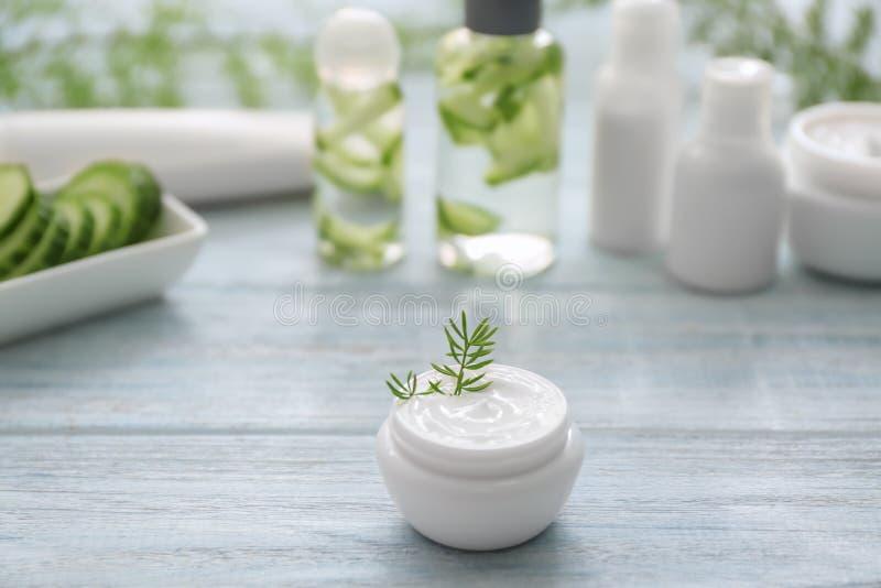 Crème avec l'extrait de fines herbes sur la table en bois blanche photo libre de droits