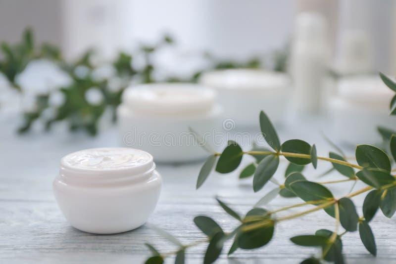 Crème avec l'extrait de fines herbes sur la table en bois blanche photos libres de droits